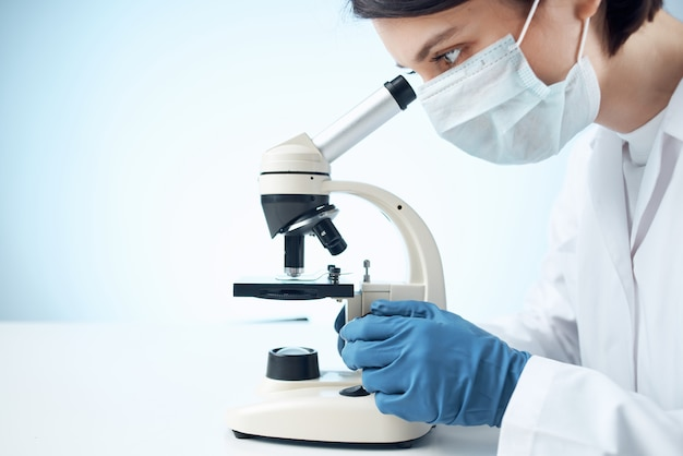 Woman in white coat microscope science work professionals