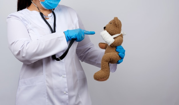 Woman in white coat with buttons holding a brown teddy bear with a white gauze bandage tied with her paw