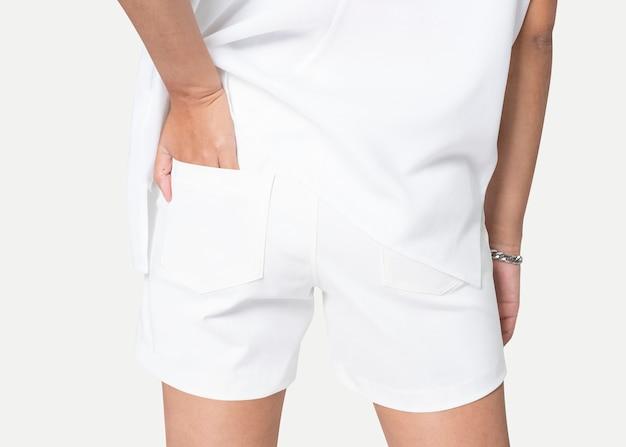 Donna in pantaloncini di jeans bianchi con la mano infilata nella tasca vista posteriore