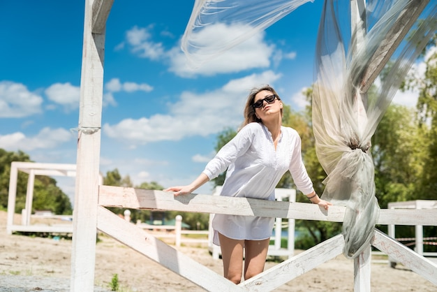Woman in white dress enjoy hot summer day near the sand beach in white wooden gazebo. vacation or relax
