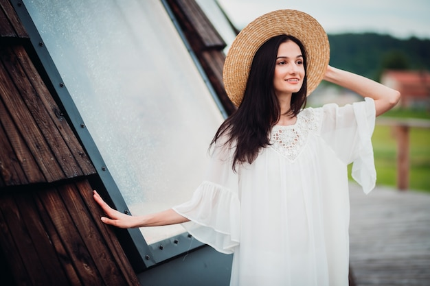 Woman in white dress and hay hat poses outside