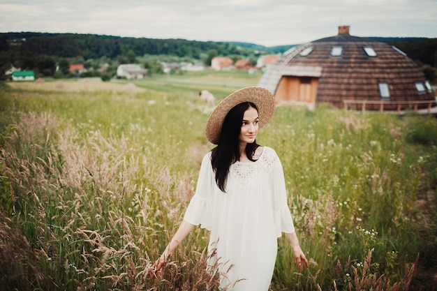 Woman in white dress and hay hat walks across the field