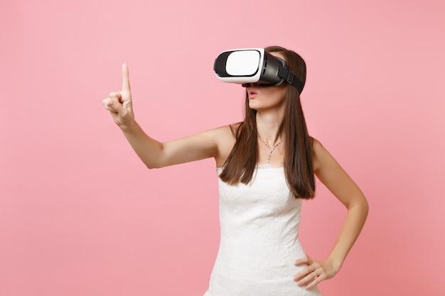 Donna in abito bianco, auricolare della realtà virtuale tocca qualcosa come premere il pulsante o indicare lo schermo virtuale mobile virtual