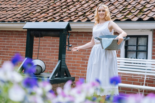 Woman in white dress holding basin near ancient artesian drawwell in village colorful violet flowers