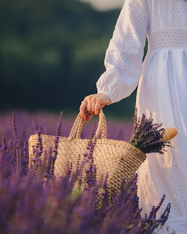 Woman in white dress holding bouquet of lavender flowers close up