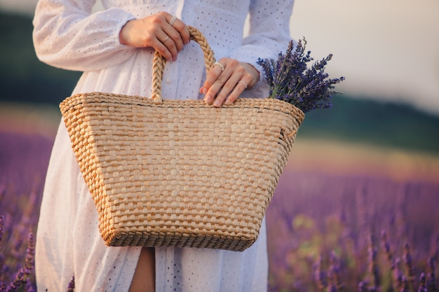 Woman in white dress holding bouquet of lavender flowers in straw bag close up