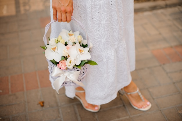 Woman in white dress holding a wicker basket of flowers