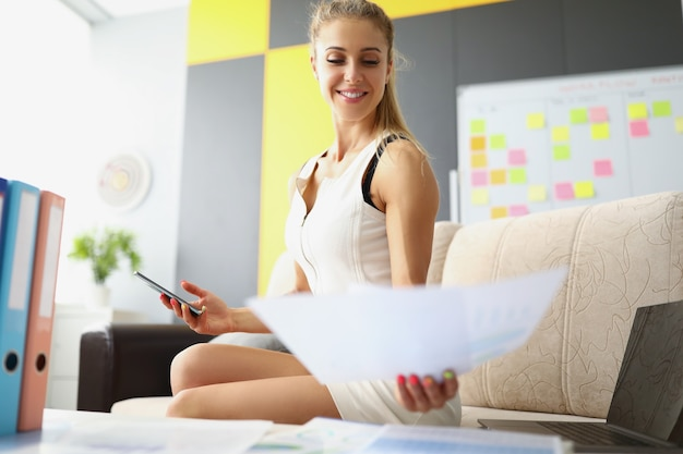 A woman in a white dress is sitting on the sofa in the office and looking at a document smiling