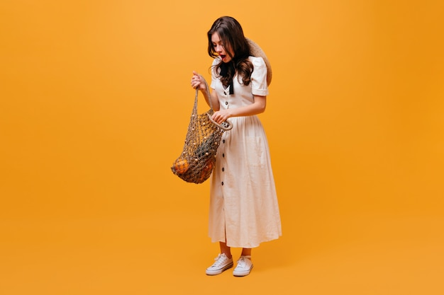 Donna in abito bianco apre la borsa della spesa con frutta e pose su sfondo arancione.