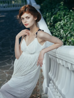 Woman in white dress outdoors romance walk green leaves luxury. high quality photo