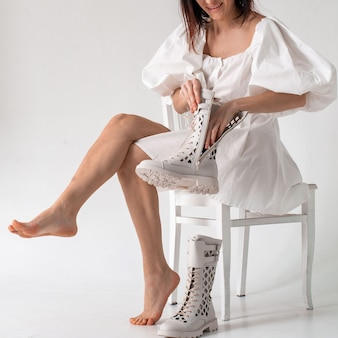 Woman in white dress puts on white summer perforated military lace-up boots on white background