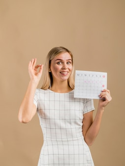 Woman in a white dress showing her period calendar