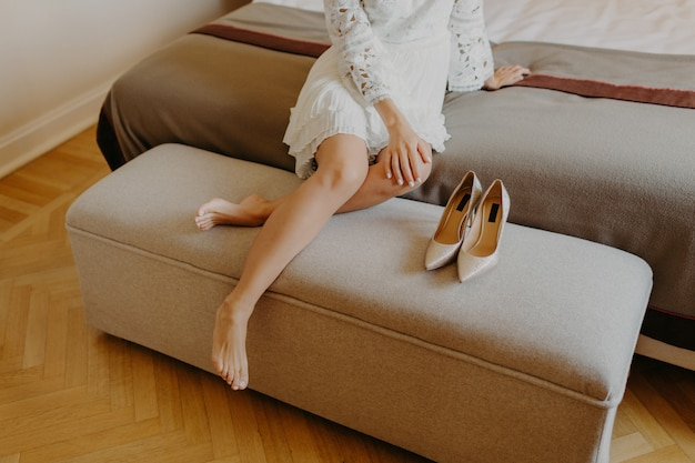 Woman in white dress, sits bare foot on comfortable sofa, rests at home after work