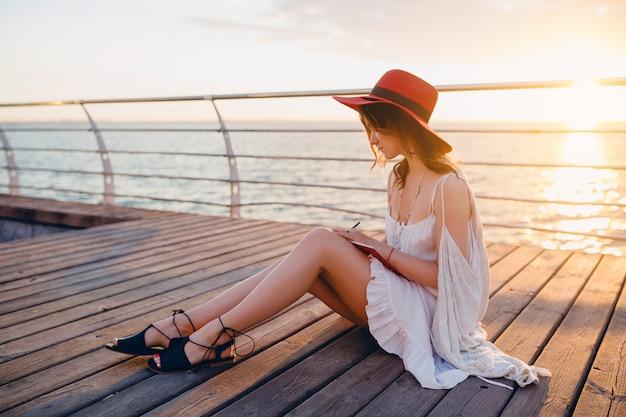 Donna in abito bianco seduto in riva al mare all'alba pensando e prendendo appunti nel diario in umore romantico indossando il cappello rosso
