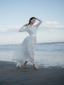 Woman in white dress walking barefoot on the sand ocean fresh air travel
