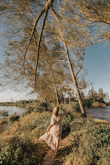 Woman in white dress walking barefoot in small grassy area surrounded by water