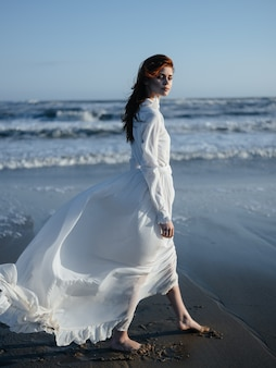 A woman in a white dress walks on the wet sand on the shore of the ocean