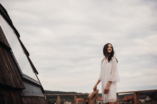 Woman in white dress whirls under cloudy sky