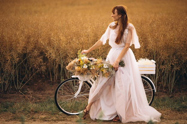 Woman in white dress with bicycle in field