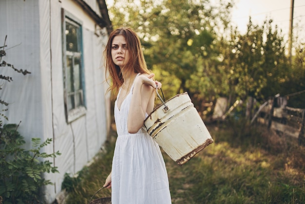 Woman in white dress with buckets in hand nature lifestyle
