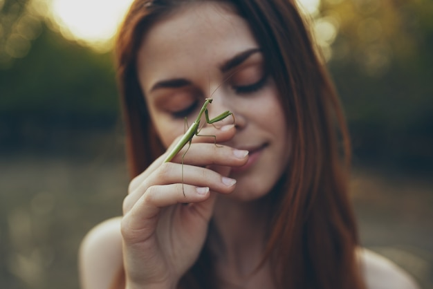 Woman in white dress with a praying mantis in hand animals. high quality photo