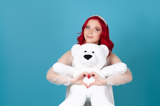 Woman in a white dress with red hair gently hugs a white teddy bear and makes a heart symbol from her fingers