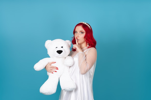Woman in white dress with red hair holds white teddy bear and index finger at mouth