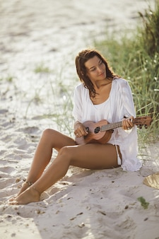 Woman in white dress with ukulele sitting down on the sand of the beach