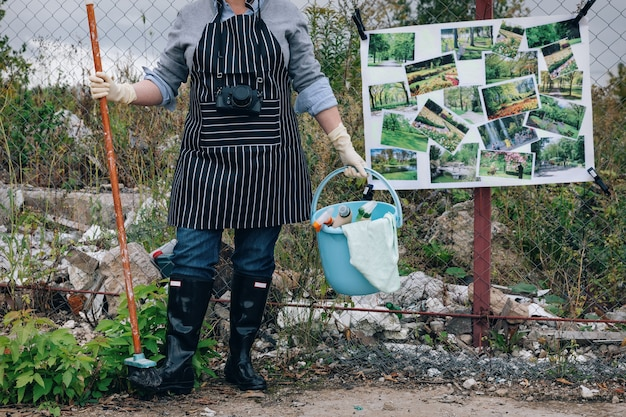Woman in white gloves with cleaning supplies near garbage dump. says no to environment polution. poster parks instead of landfills on a chain link fence