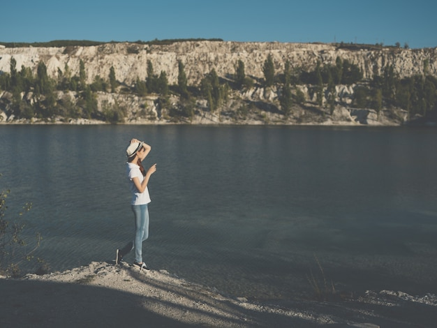 Woman in white hat near river nature vacation travel