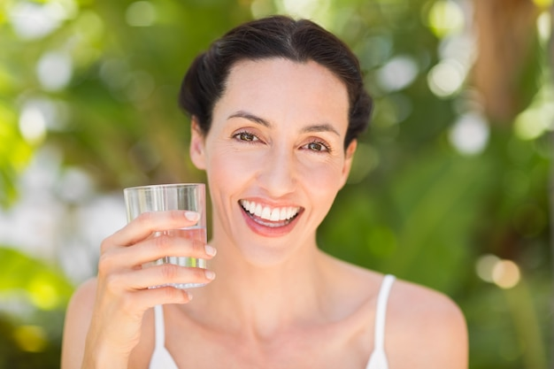 Woman in white having a glass of water