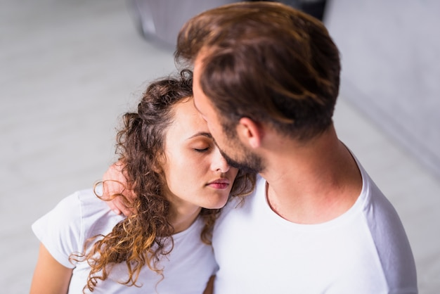Woman in white holding head on man shoulder