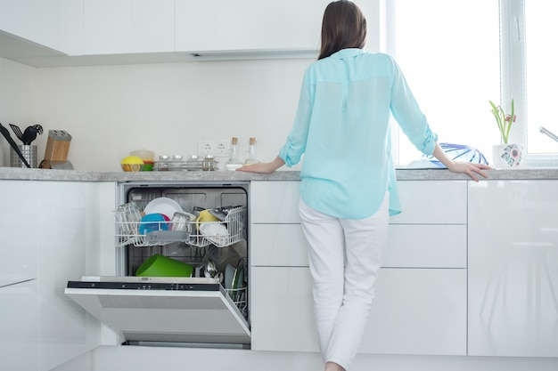 Woman in white jeans and shirt stands with her back next to an open dishwasher in kitchen interior