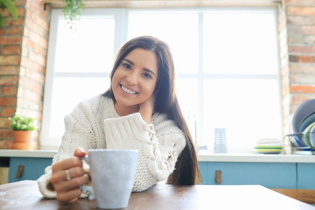 Woman in white knit sweater at home