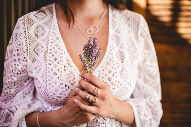 Woman in white lace crochet shirt holding a bouquet of lavender with silver necklaces