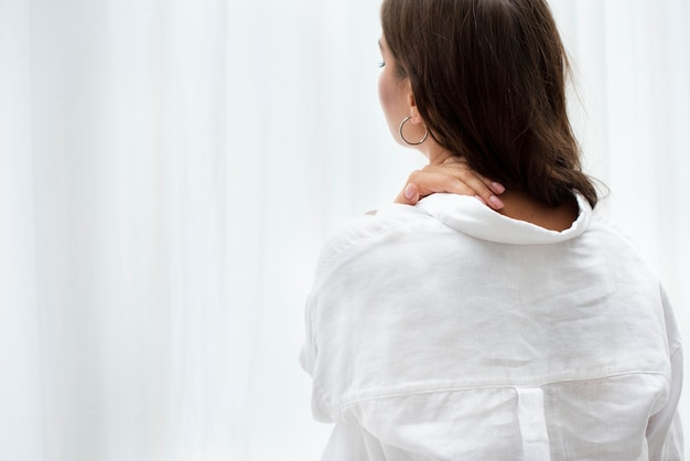 Woman in a white linen shirt touching her neck
