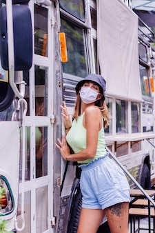 Woman in white medical mask walk around city stands by bus cafe on city square