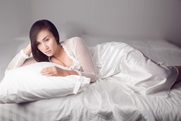 Woman in white nightgown can't sleep