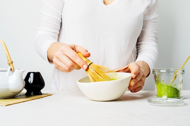 Woman in white prepare japanese green matcha tea by whipping it in a bowl with a bamboo chasen whisk