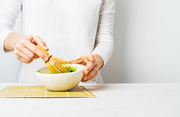 Woman in white prepare japanese green matcha tea by whipping it in a bowl