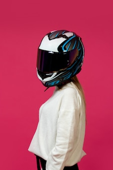 Woman in white pullover with motorcycle helmet