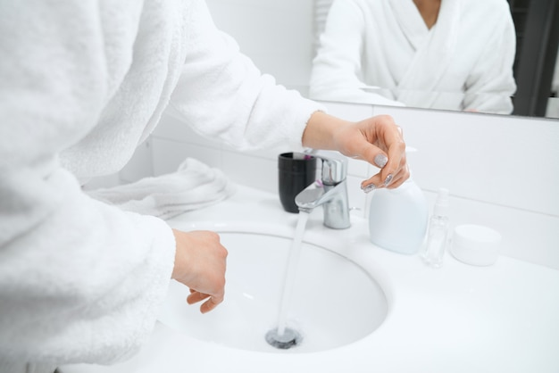 Woman in white robe standing near sink and washing hands