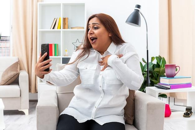 Donna in camicia bianca e pantaloni neri che fa selfie utilizzando lo smartphone felice e soddisfatta di sé seduta sulla sedia in un soggiorno luminoso