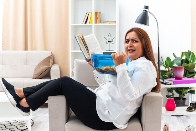 Donna in camicia bianca e pantaloni neri che si rilassa mangiando patatine e leggendo un libro mentre è seduta sulla sedia in soggiorno