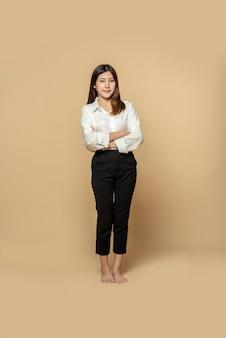 Una donna in camicia bianca e pantaloni neri è in piedi con le braccia conserte