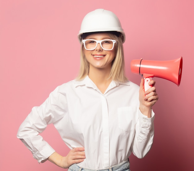 Woman in white shirt, glasses and helmet with loudspeaker