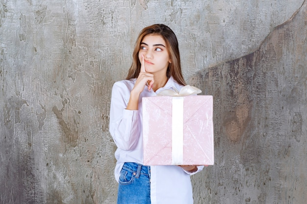 Woman in white shirt holding a pink gift box wrapped with white ribbon and looks confused and hesitating.