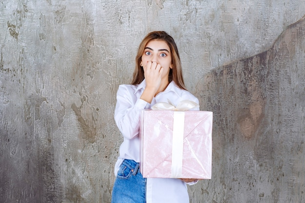 Woman in white shirt holding a pink gift box wrapped with white ribbon and looks scared or terrified.