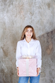 Woman in white shirt holding a pink gift box wrapped with white ribbon.