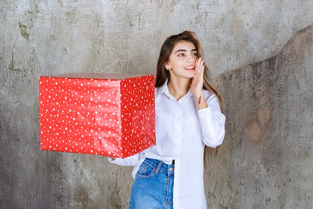 Woman in white shirt holding a red gift box with white dots on it and calling someone to handle it.